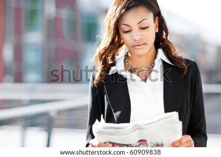 A shot of a beautiful black businesswoman reading newspaper outdoor - stock photo