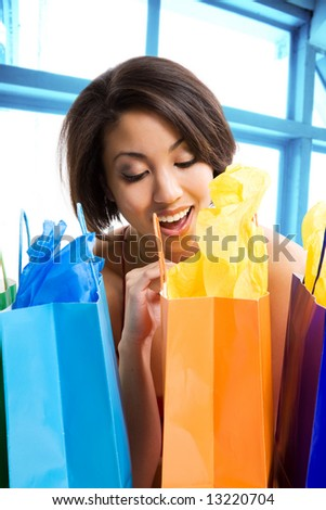 A shot of a beautiful black woman looking at her shopping bags in a store