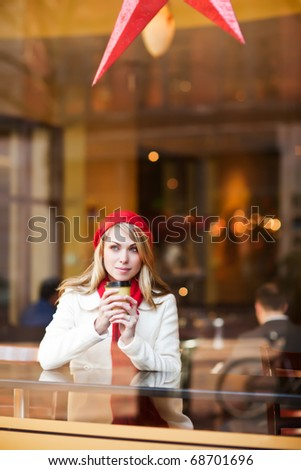 A shot of a beautiful caucasian woman drinking coffee at a cafe