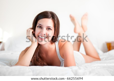 A shot of a beautiful girl lying down on the bed - stock photo