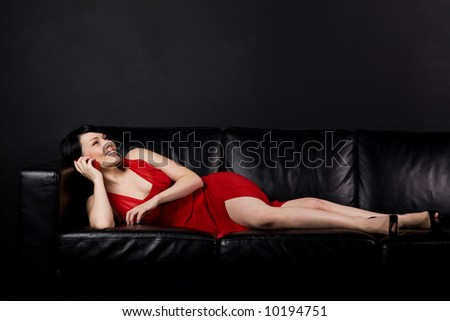 A shot of a beautiful girl lying on the sofa and talking on the cellphone - stock photo