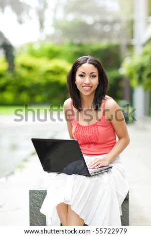 A shot of a beautiful mixed race woman with her laptop outdoor - stock photo