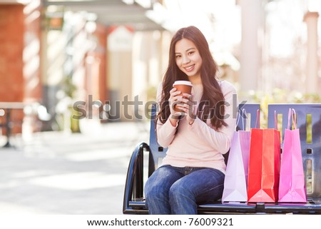 A shot of a beautiful shopping asian woman drinking coffee outdoor - stock photo