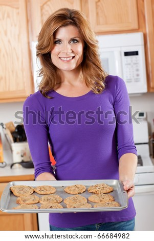 A shot of a beautiful woman baking cookies in the kitchen - stock photo