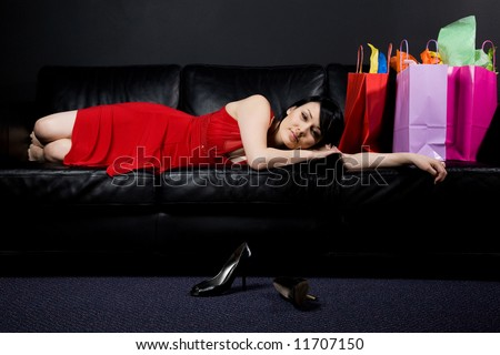 A shot of a beautiful woman resting on a couch after shopping - stock photo