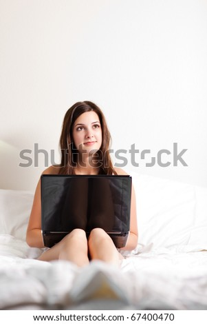 A shot of a beautiful woman using a laptop on the bed - stock photo