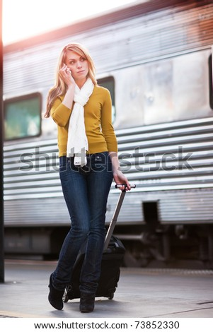 A shot of a beautiful young Caucasian woman traveling pulling a luggage and talking on the phone - stock photo