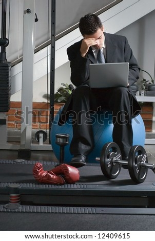A shot of a business, at the gym, using a laptop with a frustrated look on his face.