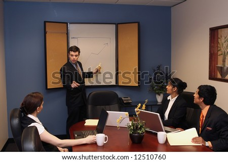 A shot of a businessman presenting in front of two businesswomen and one businessman.  His looking at the audience while pointing at the whiteboard with a banana. - stock photo