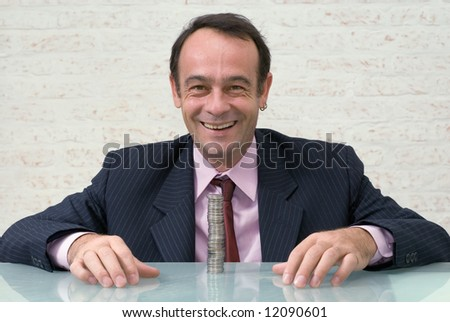 A shot of a businessman, smiling, sitting at glass desk behind a stack of coins.