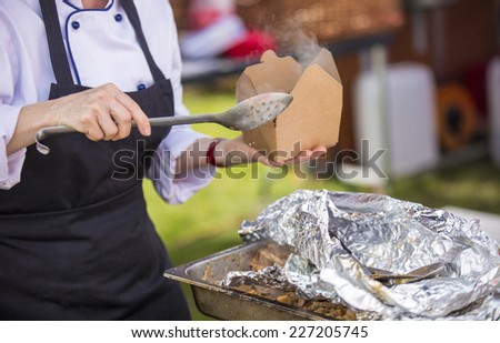 A shot of a Caterer serving takeaway food - stock photo