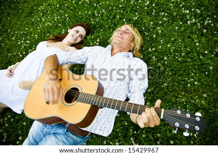 A shot of a caucasian couple lying down on the grass playing guitar and enjoying the outdoor