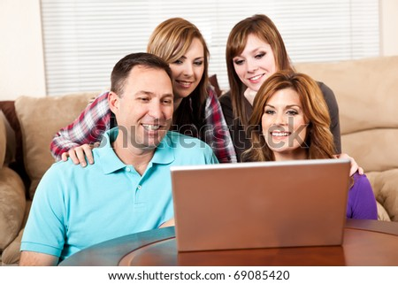 A shot of a caucasian family browsing internet on the laptop at home - stock photo