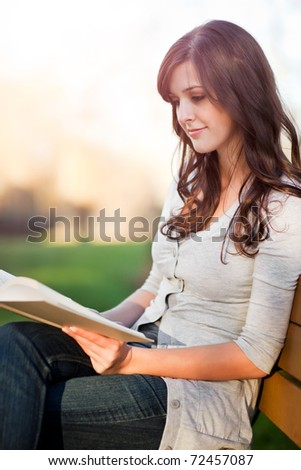 A shot of a college student reading a book - stock photo