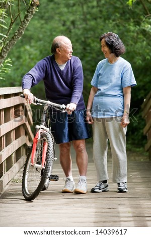A shot of a couple asian mature talking while walking and exercising at a park - stock photo