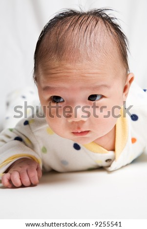 A shot of a cute asian baby boy doing a tummy time - stock photo