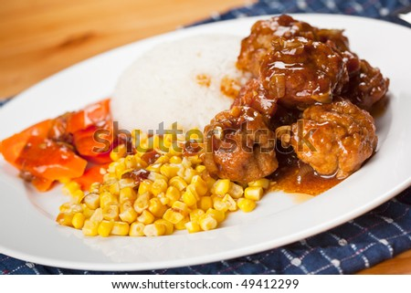 A shot of a delicious meatball and corn dish on rice dish