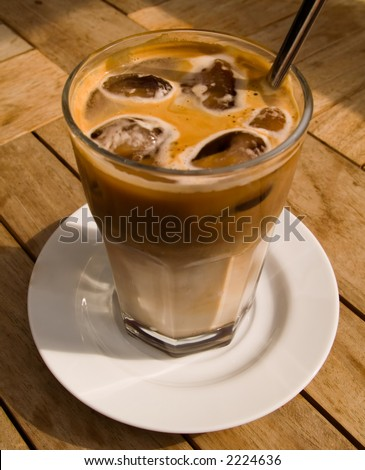 A shot of a glass of ice cold coffee on a wooden table. Back of the glass in focus.