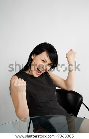 A shot of a happy and excited businesswoman at the office - stock photo