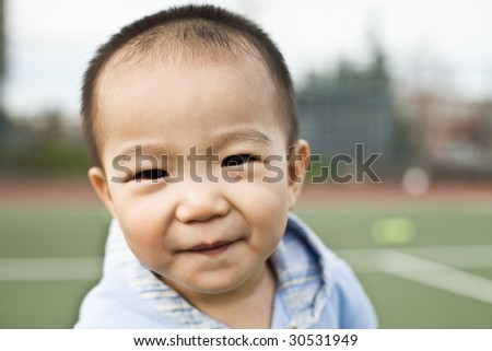 A shot of a happy asian boy smiling - stock photo
