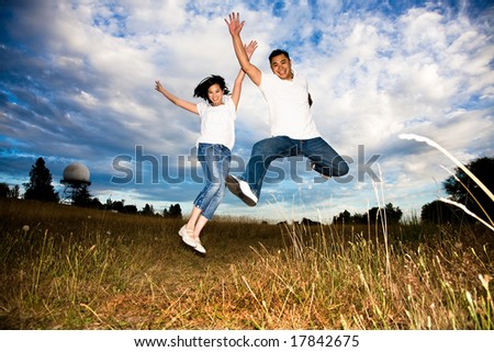 A shot of a happy asian couple jumping for joy - stock photo