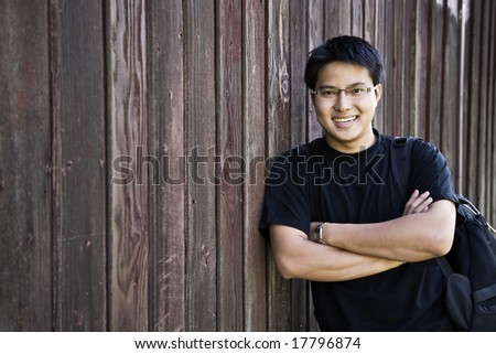 A shot of a happy asian student carrying a backpack - stock photo