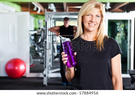 A shot of a happy caucasian female athlete holding a water bottle in a gym - stock photo