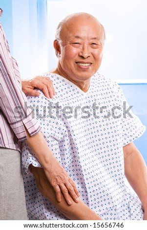 A shot of a happy senior asian male accompanied by his wife in the hospital - stock photo