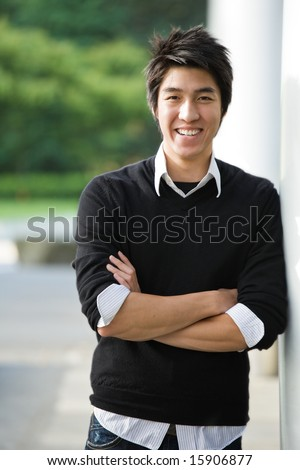 A shot of a happy young asian student - stock photo