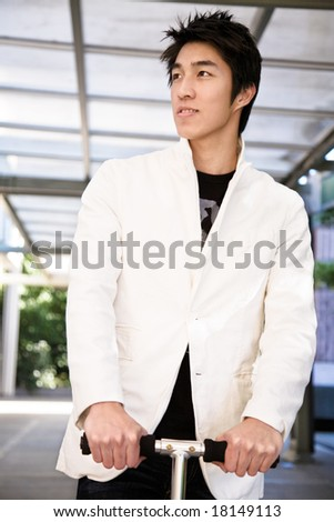 A shot of a hip young asian male riding a scooter - stock photo