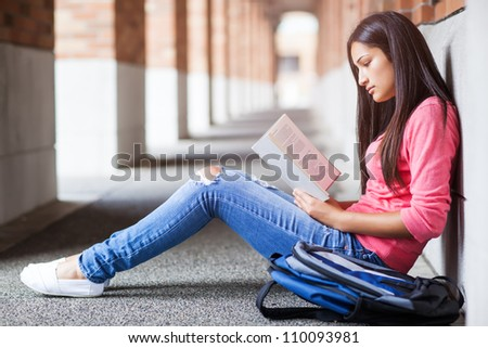 A shot of a hispanic college student studying on campus - stock photo