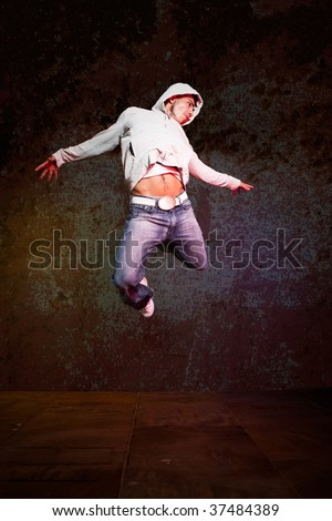 A shot of a hispanic male doing a hip-hop dance jumping in the air