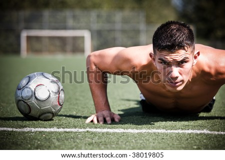 A shot of a hispanic soccer or football player doing a push-up - stock photo