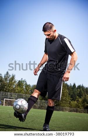 A shot of a hispanic soccer or football player kicking a ball - stock photo
