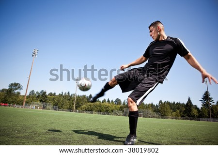 A shot of a hispanic soccer or football player kicking a ball - stock photo