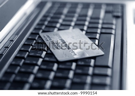 A shot of a laptop and a credit card in an office environment, can be used as e-commerce concept - stock photo