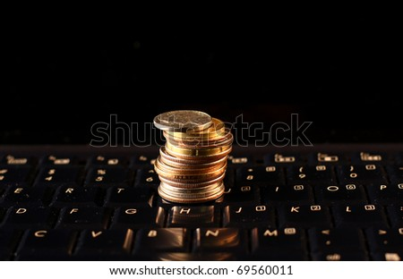 A shot of a laptop and coins - stock photo