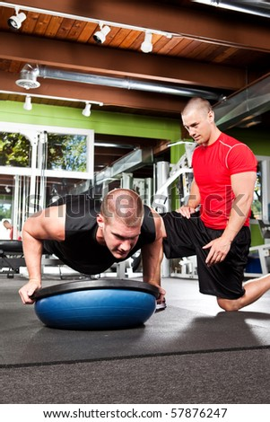 A shot of a male personal trainer assisting a male athlete doing push-up