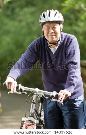 A shot of a mature asian man riding a bike - stock photo