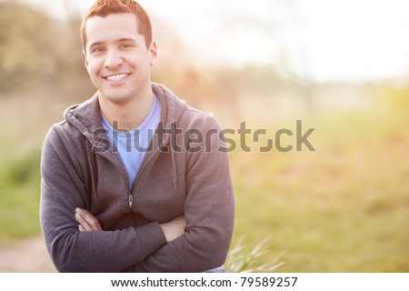 A shot of a mixed race man smiling outside - stock photo