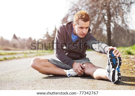 A shot of a mixed race man stretching outdoor