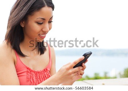 A shot of a mixed race woman texting on her cell phone - stock photo
