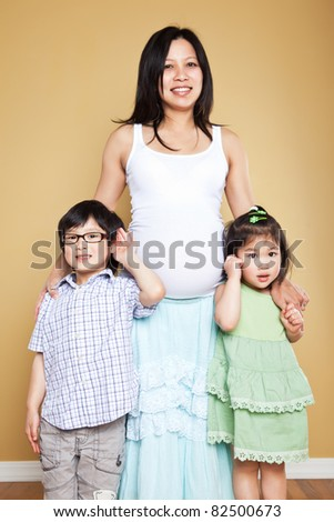 A shot of a pregnant Asian mother with her two kids - stock photo