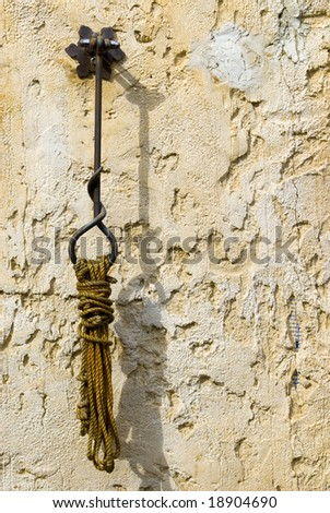 A shot of a rope which is hanging form a handcrafted hook