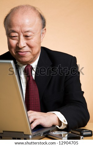 A shot of a senior asian businessman working on his laptop - stock photo