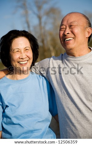 A shot of a senior asian couple having fun outdoor - stock photo