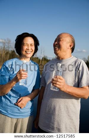 A shot of a senior asian couple having fun outdoor - stock photo