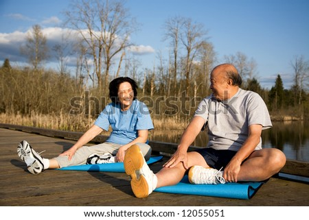 A shot of a senior asian couple stretching before exercise - stock photo