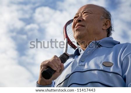 A shot of a senior asian man holding a tennis racquet - stock photo