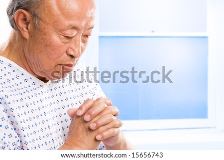 A shot of a senior asian man praying in hospital - stock photo